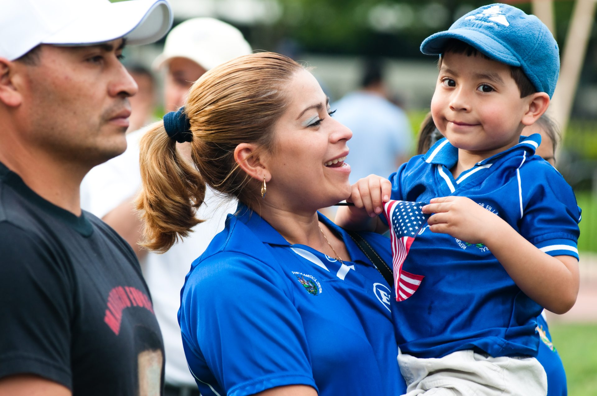 A Latina mother is holding her child who has a small US flag in his hands